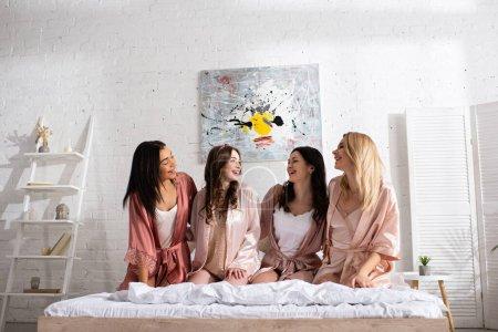 Photo pour Femmes afro-américaines et européennes riant sur le lit dans la chambre au enterrement de vie de jeune fille - image libre de droit