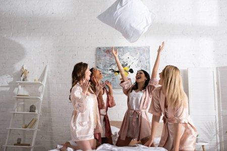 Photo pour Amis multiculturels excités vomissant oreiller sur le lit dans la chambre à la fête de célibataire - image libre de droit