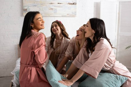 Photo for Excited multicultural women together with pillows on bed at bachelorette party - Royalty Free Image
