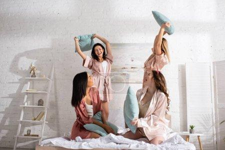 Photo pour Amis multiculturels avec des oreillers s'amuser ensemble sur le lit dans la chambre à la fête de célibataire - image libre de droit