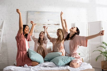 Photo for Happy multicultural friends with hands in air smiling with pillows on bed at bachelorette party - Royalty Free Image