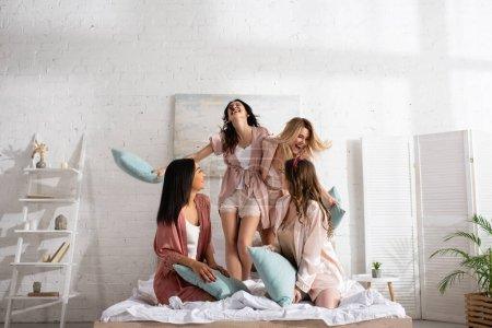 Photo pour Heureux amis multiculturels rire et s'amuser avec des oreillers sur le lit au enterrement de vie de jeune fille - image libre de droit