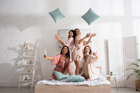Happy and positive multicultural women smiling, throwing up pillows and taking selfie with smartphones on bed