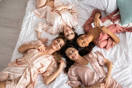 Photo for Top view of multiethnic women smiling, looking at camera and lying on bed at bachelorette party - Royalty Free Image