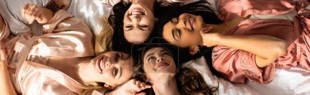 Photo pour Vue du dessus des femmes multiethniques souriant et se reposant sur le lit à la fête de célibataire, vue panoramique - image libre de droit