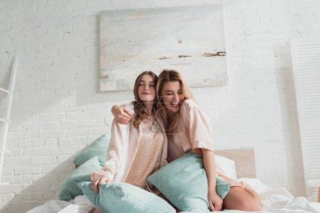 Photo pour Attractives femmes étreignant et souriant avec des oreillers sur le lit à la fête de célibataire - image libre de droit