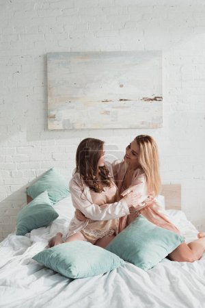 Photo pour Attractives femmes étreignant, souriant et se regardant avec des oreillers sur le lit à enterrement de vie de jeune fille - image libre de droit