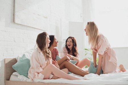 Photo pour Femmes multiculturelles riant pendant la célibataire sur le lit au enterrement de vie de jeune fille - image libre de droit