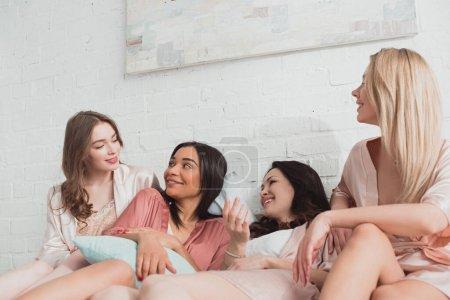 Photo pour Femmes multiculturelles se regardant et souriant sur le lit au enterrement de vie de garçon - image libre de droit