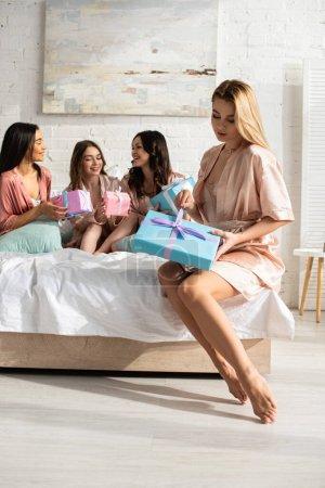 Photo pour Concentration sélective de la boîte cadeau d'ouverture de fille blonde avec des amis multiculturels à la fête de célibataire sur le lit - image libre de droit