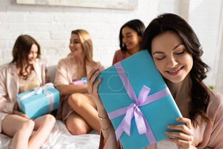 Photo pour Concentration sélective de la fille brune avec des amis présents près multiethnique tenant des boîtes-cadeaux sur le lit à la fête de célibataire - image libre de droit