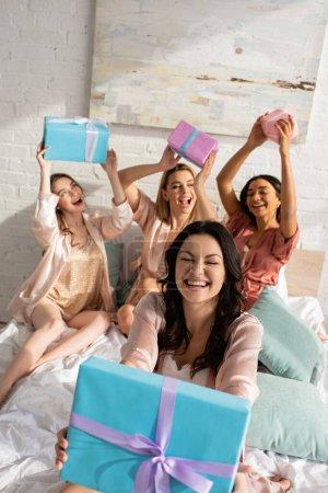 Photo pour Foyer sélectif de fille brune montrant présent près d'amis multiculturels avec des boîtes-cadeaux souriant sur le lit - image libre de droit