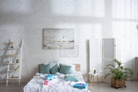 Photo pour Lit avec oreillers et cadeaux dans une chambre lumineuse et spacieuse - image libre de droit