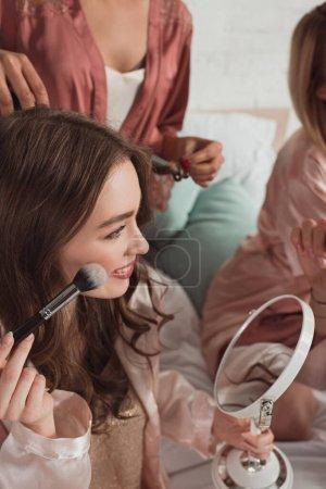 Photo pour Vue recadrée de femmes multiethniques se maquillant et faisant coiffure avec fer à friser dans la chambre - image libre de droit