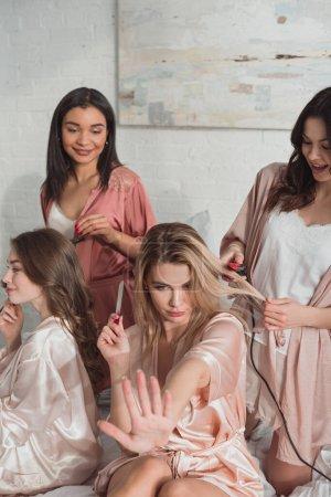 Photo pour Fille blonde avec lime à ongles regardant manucure avec des amis multiethniques sur le lit à la fête de célibataire - image libre de droit