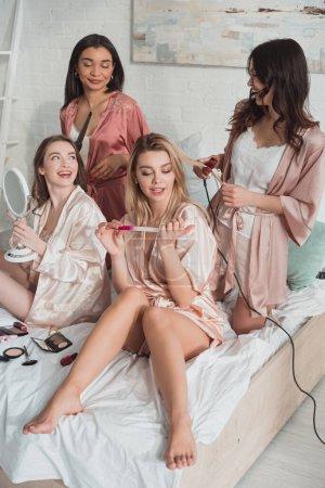Photo pour Amis multiculturels faisant coiffures sur le lit à la fête de célibataire - image libre de droit