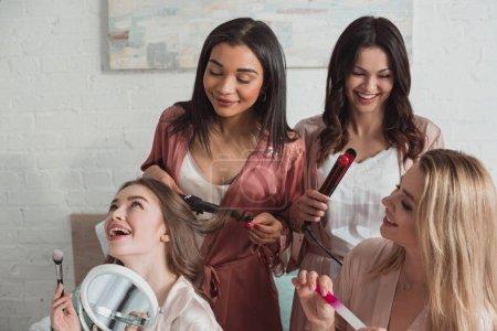 Foto de Amigos multiculturales haciendo peinados con mordeduras y sonriendo en la fiesta bachelorette. - Imagen libre de derechos