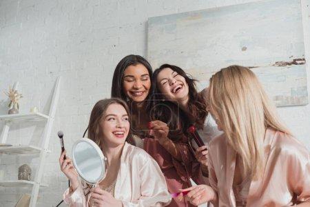Photo pour Femmes multiethniques coiffantes, manucures et rires à la bachelorette - image libre de droit