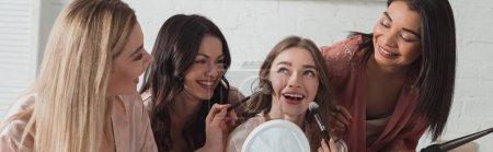 Photo pour Femmes multiculturelles avec maquillage avec pinceaux cosmétiques sur la mariée, souriant ensemble dans la chambre, vue panoramique - image libre de droit