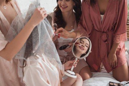 Photo pour Femmes multiethniques se maquillant sur la mariée dans la chambre au enterrement de vie de jeune fille - image libre de droit