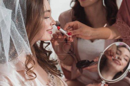 Photo pour Vue recadrée de femmes multiethniques mettant maquillage avec pinceau cosmétique et rouge à lèvres sur mariée sur fond blanc - image libre de droit