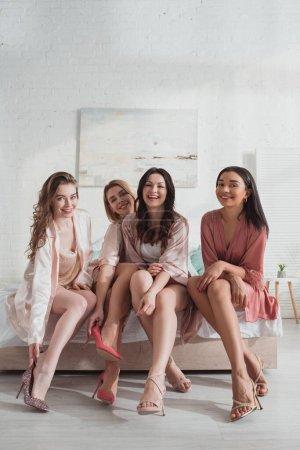 Photo pour Femmes multiculturelles souriant et regardant la caméra sur le lit - image libre de droit