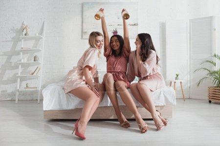 Photo pour Heureuse mariée afro-américaine tenant des bouteilles de champagne avec des amis au lit au enterrement de vie de jeune fille - image libre de droit