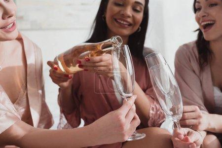 Photo pour Vue partielle de la fille afro-américaine versant du champagne dans des verres avec des amis à la fête de célibataire - image libre de droit