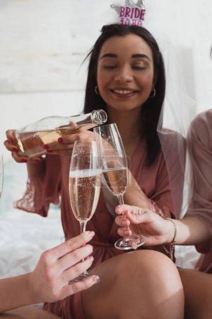 Photo pour Vue recadrée de la mariée afro-américaine versant du champagne dans des verres avec des amis à la fête de célibataire - image libre de droit