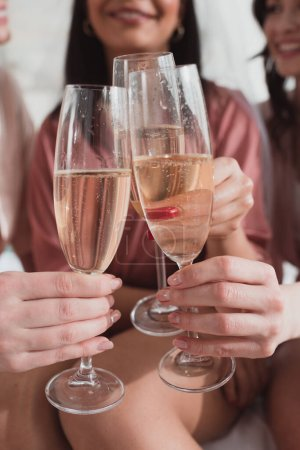 Photo pour Vue recadrée de femmes multiethniques cliquetis avec des verres de champagne à la fête de célibataire - image libre de droit