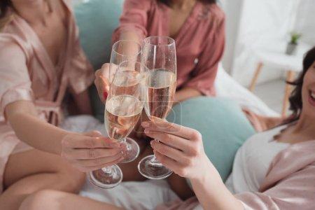 Photo pour Coupé vue de multiethnique amis clinking avec champagne verres à enterrement de vie de jeune fille - image libre de droit