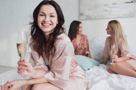 Photo pour Foyer sélectif de fille brune regardant la caméra, souriant et tenant verre de champagne avec des amis multiethniques sur le lit - image libre de droit