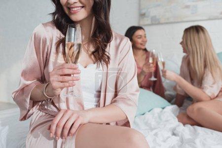 Photo pour Vue recadrée de fille brune souriant et tenant verre de champagne avec des amis multiethniques sur le lit - image libre de droit