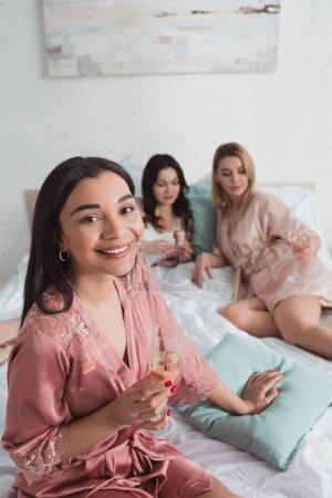 Photo pour Vue grand angle de fille afro-américaine regardant la caméra et tenant verre de champagne avec des amis sur le lit - image libre de droit