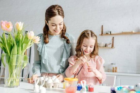 Photo for Selective focus of child and mother near tulips and easter eggs - Royalty Free Image
