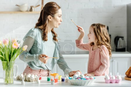 Photo for Side view of cheerful mother and happy daughter looking at each other near painted easter eggs and flowers - Royalty Free Image