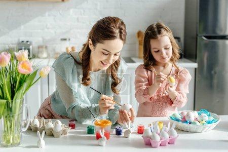 Photo pour Foyer sélectif de l'enfant mignon et de la mère peignant des oeufs de Pâques près des tulipes - image libre de droit