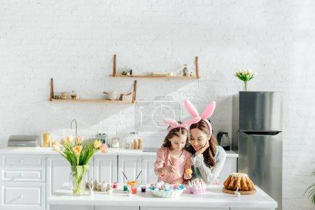 Photo for Happy kid and mother with bunny ears near chicken eggs, decorative rabbits, easter bread and tulips - Royalty Free Image
