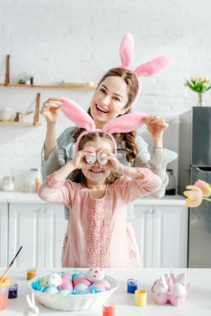 Photo for Happy mother touching bunny ears on daughter covering eyes with chicken eggs near tulips - Royalty Free Image