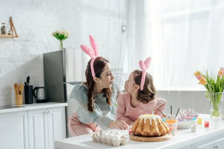 Photo for Happy mother and daughter in bunny ears looking at each other near easter eggs - Royalty Free Image