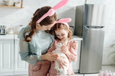 Photo for Mother hugging kid in bunny ears with toy rabbit - Royalty Free Image
