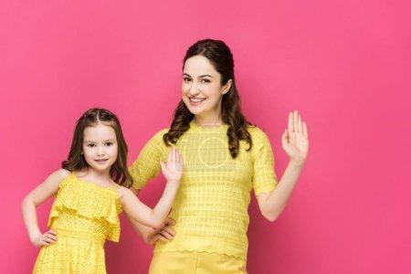 Photo pour Heureux mère et fille agitant les mains isolé sur rose - image libre de droit