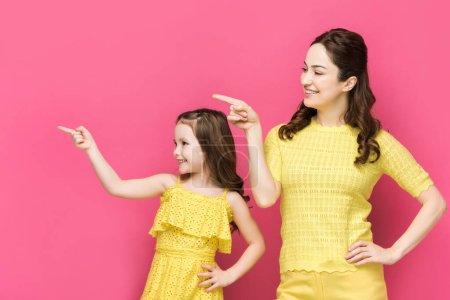 Photo pour Heureux mère et enfant pointant avec les doigts isolés sur rose - image libre de droit
