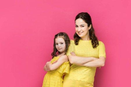 Photo pour Une femme heureuse et un enfant debout, les bras croisés isolés sur le rose - image libre de droit