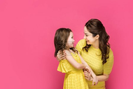 Photo for Cheerful mother looking at cute daughter isolated on pink - Royalty Free Image