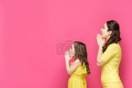 Photo pour Profil de la mère et de la fille avec les mains priantes isolées sur rose - image libre de droit