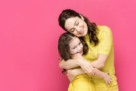 Photo for Cheerful mother and daughter hugging isolated on pink - Royalty Free Image