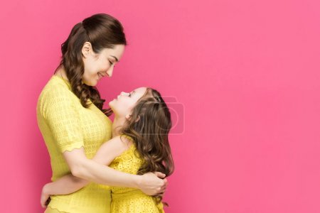 Photo for Profile of cheerful mother and daughter hugging isolated on pink - Royalty Free Image
