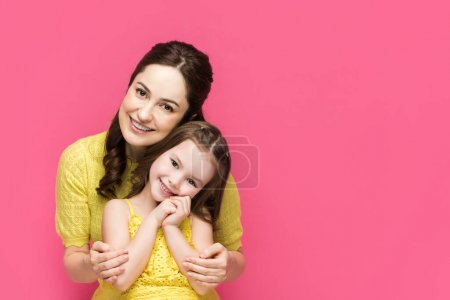 Photo for Cheerful mother hugging cute daughter isolated on pink - Royalty Free Image