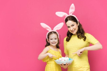Photo for Happy mother and daughter in bunny ears pointing with fingers at easter eggs isolated on pink - Royalty Free Image